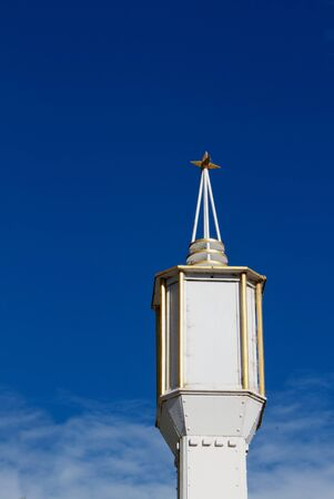 Decco White and Gold Lamp with star on top against deep blue sky photo