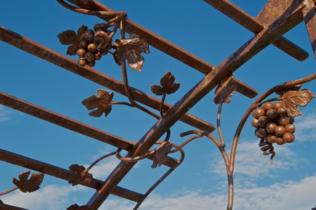 latticework: Brown iron trellis with grape vine design against a blue sky with clouds
