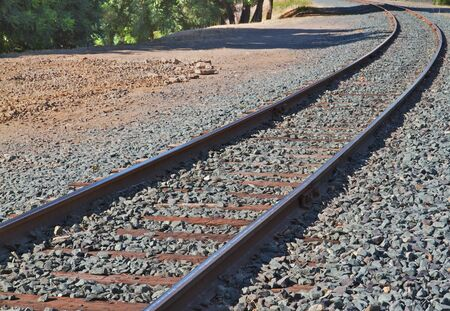 curve: Brightly lit railroad track curve with gray gravel on either side