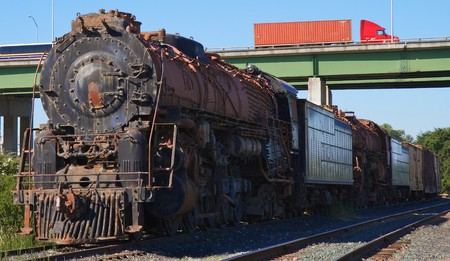 Old rusted train engine and cars against background of elevated highway with truck photo