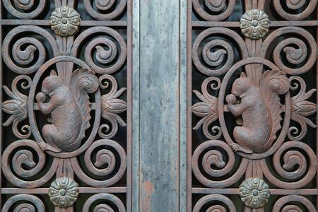 Close up portion of a wrought iron door with squirrels photo