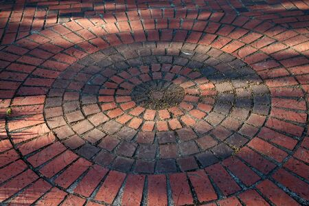 Circles of different colored and sized red bricks photo