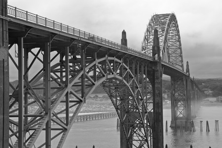 repetitious: Old green metal bridge disappearing into the mist as a black and white image