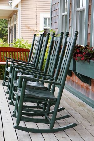 Four green wooden rocking chairs on a porch with partial wood swing Banco de Imagens - 7565665