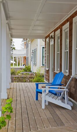 Blue and white adirondack chairs on a the wood porch of a brown shake home Stock Photo - 7565662