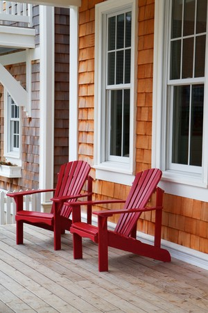 adirondack: Two red Adirondack chairs on a wood deck against a brown wood shake home Stock Photo