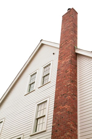 Side of older style white house with tall red brick chimney Banco de Imagens