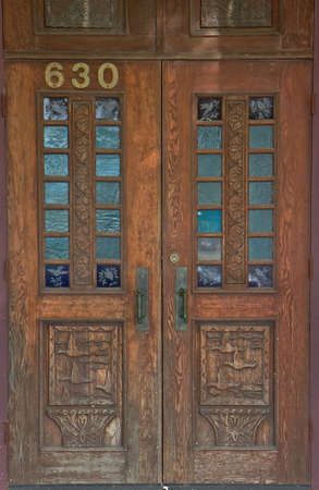 Old worn and weathered wood door with duck and bird carvings and etching photo