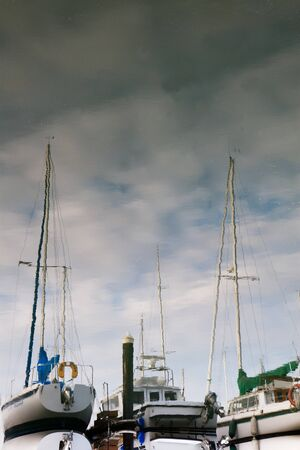 Reflections of sailboats in still water with partly cloudy skies photo