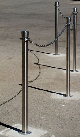 Stainless steel cue chain and posts on concrete Stock Photo - 7657902