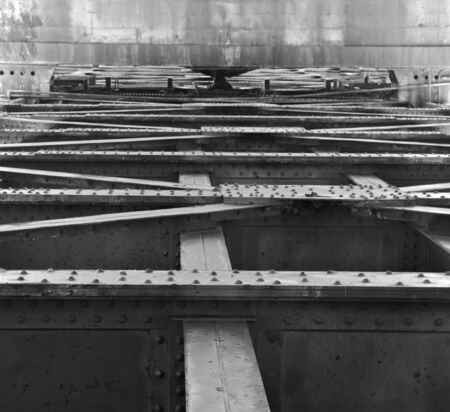 Framework of old steel beams and girders with backdrop of concrete wall photo