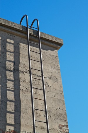 Steel ladder up concrete wall with blue sky background Stock Photo - 7742101