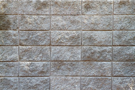 Several rows of a rough textured concrete block wall photo