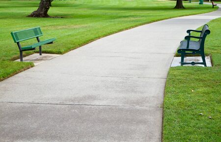Two green metal benches across a large concrete pathway in a park photo