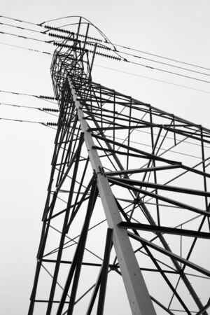 Side view of electric power tower looking from the base to the top against cloudy sky photo