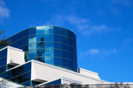 Cylindrical and flat glass building surfaces reflect trees and blue sky Stock Photo - 7858608