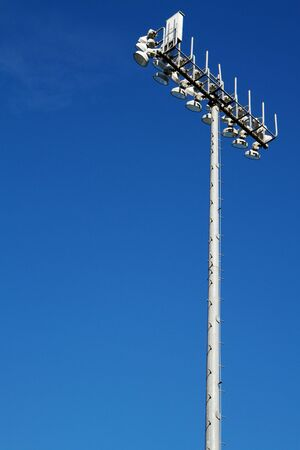 Sporting Field lights on top of tall steel pole with dark blue sky background photo