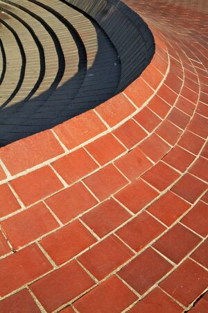 Red curved brick wall that comes to a ridge with steps on the other side