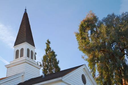 Old traditional community church steeple against blue sky and clouds and trees