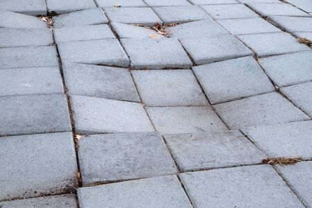 Sidewalk of concrete tiles that are starting to sink and have created a depression Banco de Imagens