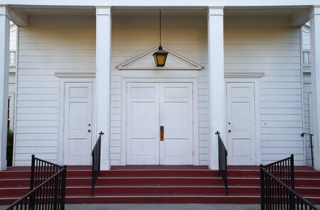 Red stairs leading to four white church doors wth black railing photo