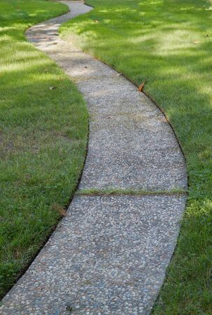 Curved stone and concrete walkway through green grass lawn