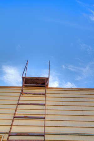 rungs: Escalera de acero de techo en madera de amarillo viejo edificio con cielo azul blanco cloudscape  Foto de archivo