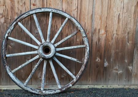 風化レッドウッド壁に対して古い荷馬車の車輪