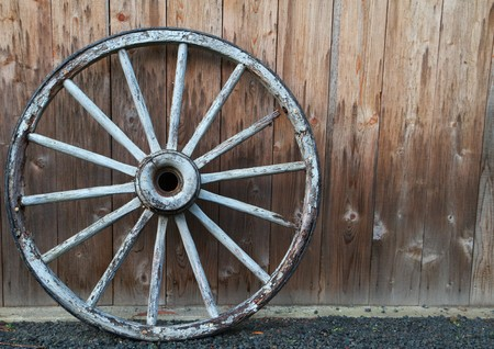 Old wagon wheel against a weathered redwood wall