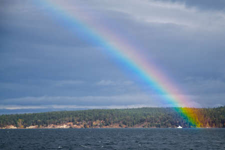 arching: Bright Rainbow arching over Discovery Bay in Washington