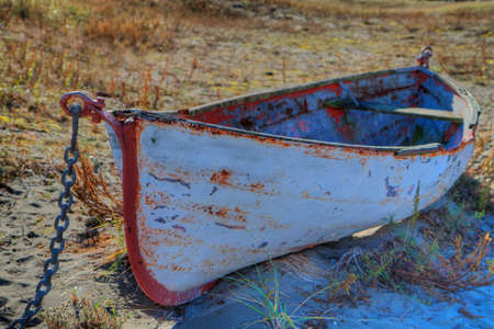 HDR image of a red and white Land locked Boat  on sand dunes