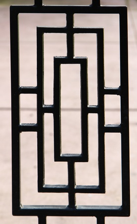 black, near silhouette, of a portion of a deco designed wrought iron gate photo