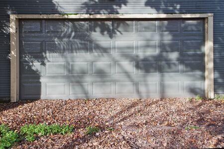 Gray garage door on similar color door during autumn with leaves in driveway photo
