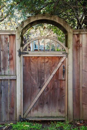Arched entry of a worn Redwood Fence Door photo