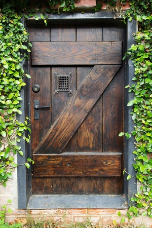 locked: Small Spanish style dark stained wood door to secret garden with grated window
