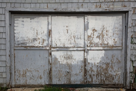 Old weathered and worn out gray garage door bordered by   wood shingle wall