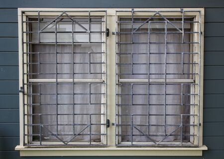 lattice window: Metal barred or grated security installed on two windows Stock Photo