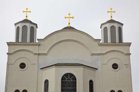 Three gold crosses on top of a stucco Serbian church