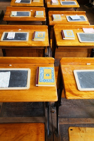 Rows of  wood and metal desks at a an old school house in Sacramento with slates and books