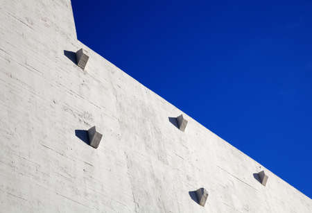 Portion of a sun lit concrete warehouse wall with sharp angles, jutting abutments, and against a dark blue sky photo