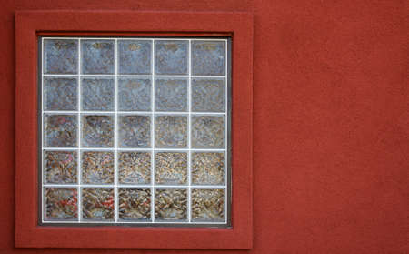 Glass block window with a red textured stucco wall photo