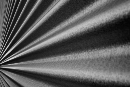 Black and white image of a steel metallic corrugated wall converging to a point