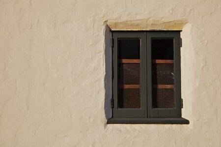 Old green wood window inset in a beige or tan stucco wall Stock Photo - 8818707