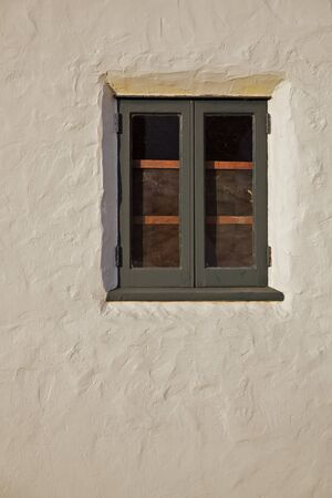 Old green wood window inset in a beige or tan stucco wall Stock Photo - 8818715