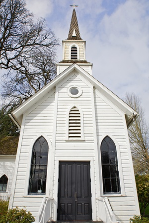 Small old Chruch with two windows and black door with trees and sky backround