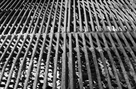 Close up of a well used steel grill on a park barbeque Stock Photo