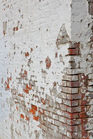 White painted red brick wall with cracked and peeling paint
