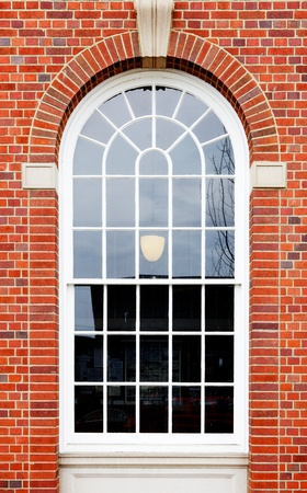 White painted wood arched window in a red brick wall 스톡 콘텐츠