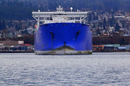 Huge blue freighter bow pointed toward viewer with port town in background photo