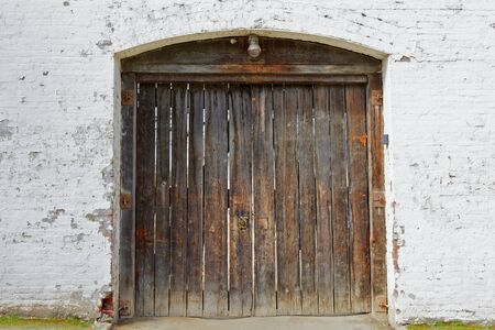 Weathered and battered old stained wood fort doors on a white washed brick wall Stock Photo